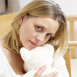 5515868 - sad mother sitting in empty nursery